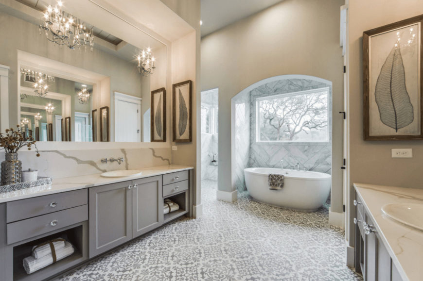 Fabulous bathroom designed with leaf wall arts and fancy candle sconces mounted on the frameless mirrors. It has facing gray vanities and a pedestal tub by the picture window overlooking the outdoor scenery.