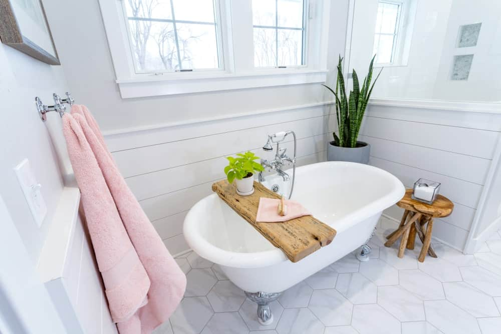Bright bathroom offers a clawfoot tub topped with a rustic tray complementing the stool that sits on hex tile flooring. There's a potted plant on the side bringing a refreshing ambiance to the room.