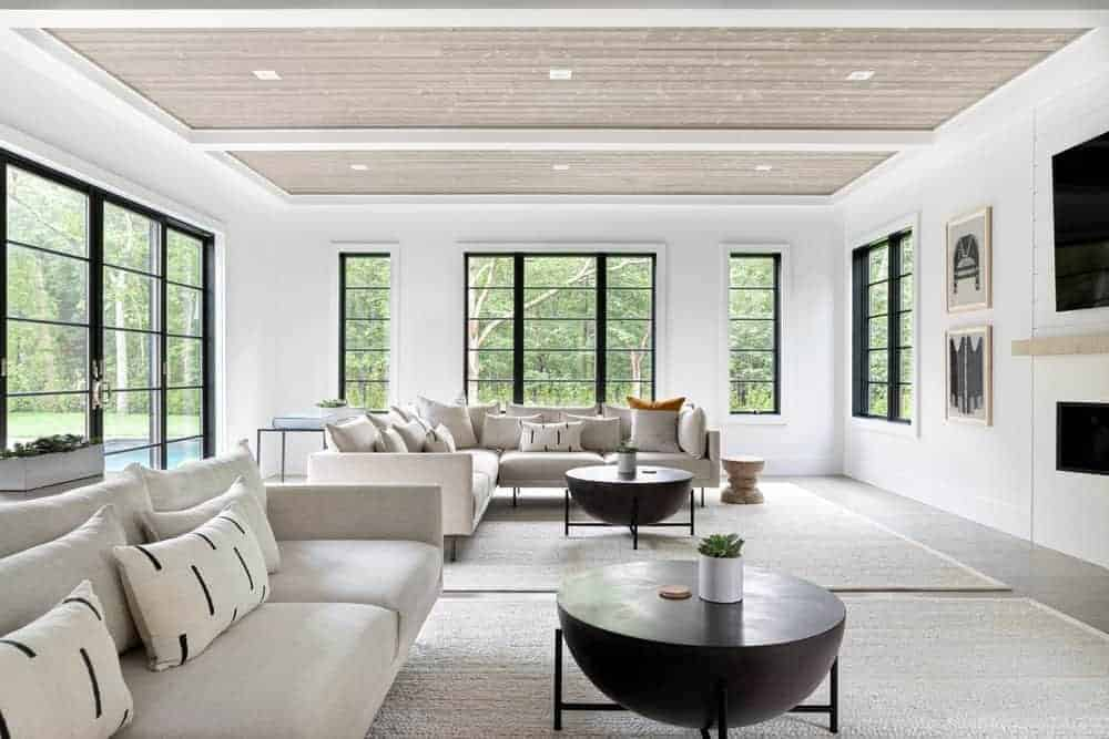 This bright and spacious Farmhouse-style living room has enough space for two light gray sectional sofas that is both paired with decorative round dark coffee tables that stand out against the light gray area rug that is brightened by the surrounding windows.