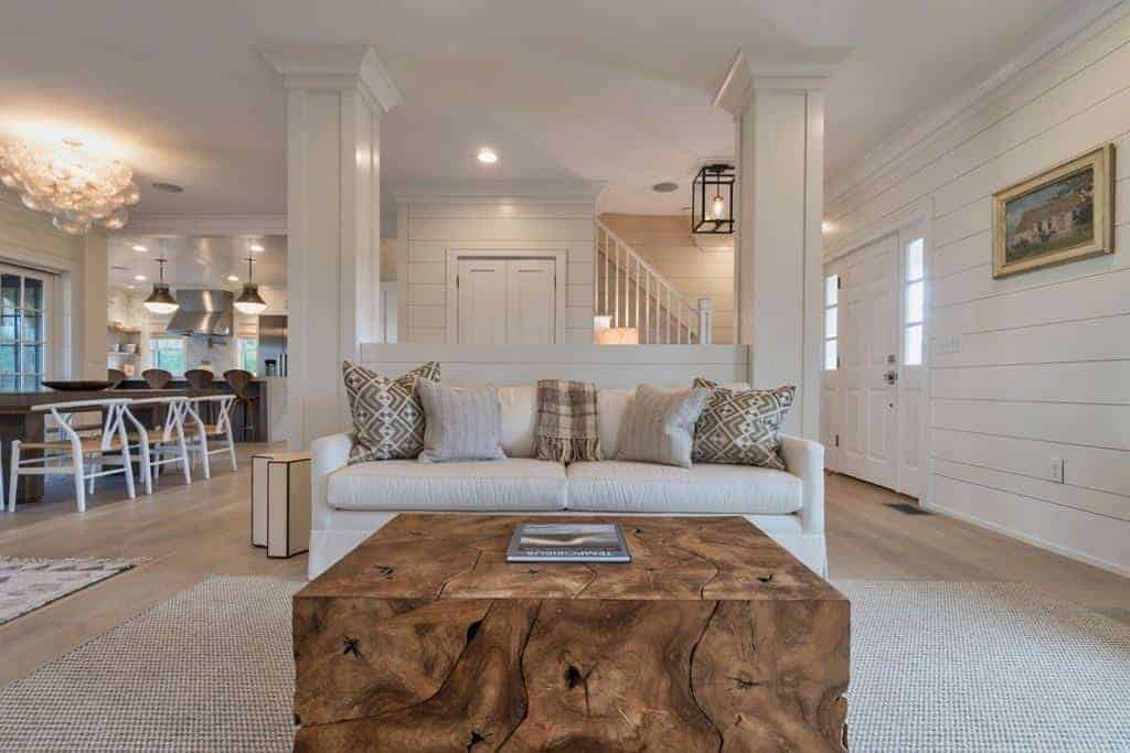 The highlight of this Farmhouse-style living room is the charming wooden coffee table that brings a rustic quality to the light gray area rug over the light hardwood flooring, light gray sofa and light gray walls with a shiplap plank finish.