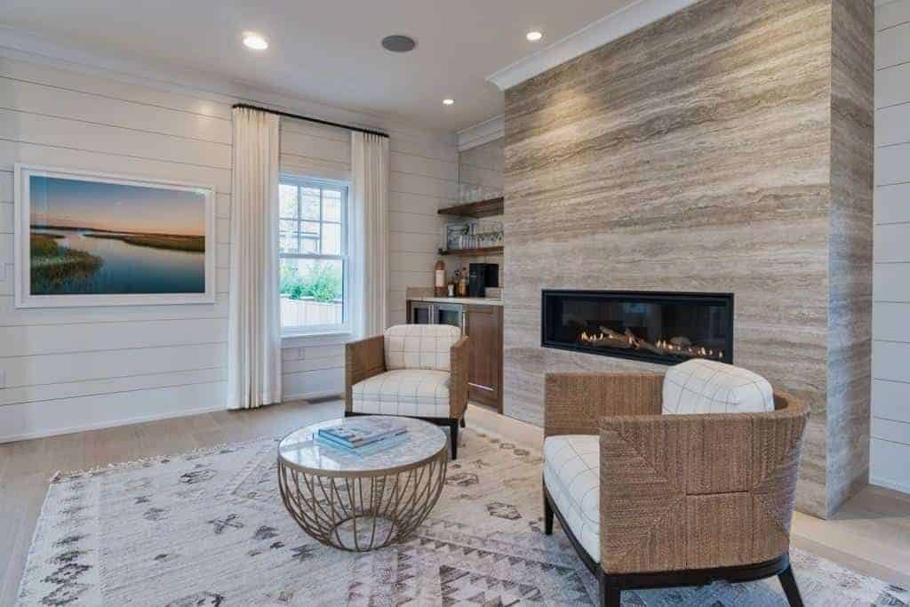 This simple living room has a couple of rustic woven wicker armchairs with white patterned cushions that match the distressed patterned area rug facing a modern glass enclosed fireplace inlaid in a large light gray column in the middle of the armchairs.