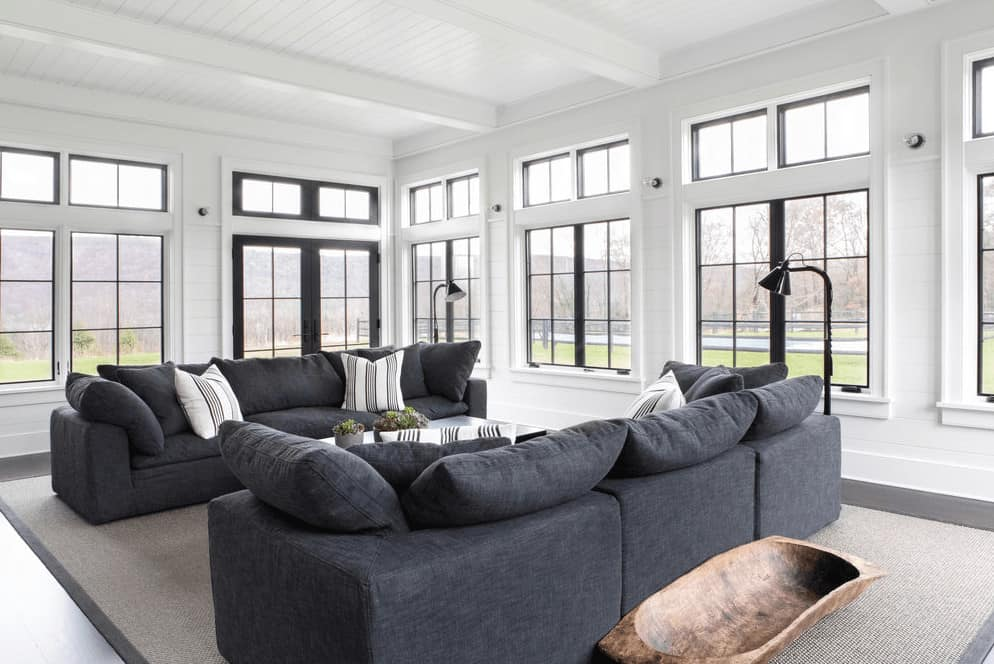 This is a bright Farmhouse-style living room with a white wooden ceiling that has white exposed wooden beams matching with the white walls that bring in an abundance of natural lighting through the surrounding tall windows that lighten up the gray comfortable sofas.