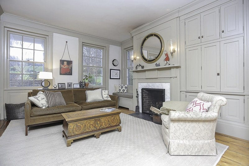 The light gray ceiling and light gray patterned area rug matches with the light gray wooden finish of the walls that has built in cabinets on one side, a fireplace in the middle with a wall-mounted mirror on top and a charming reading nook at the corner by the windows.