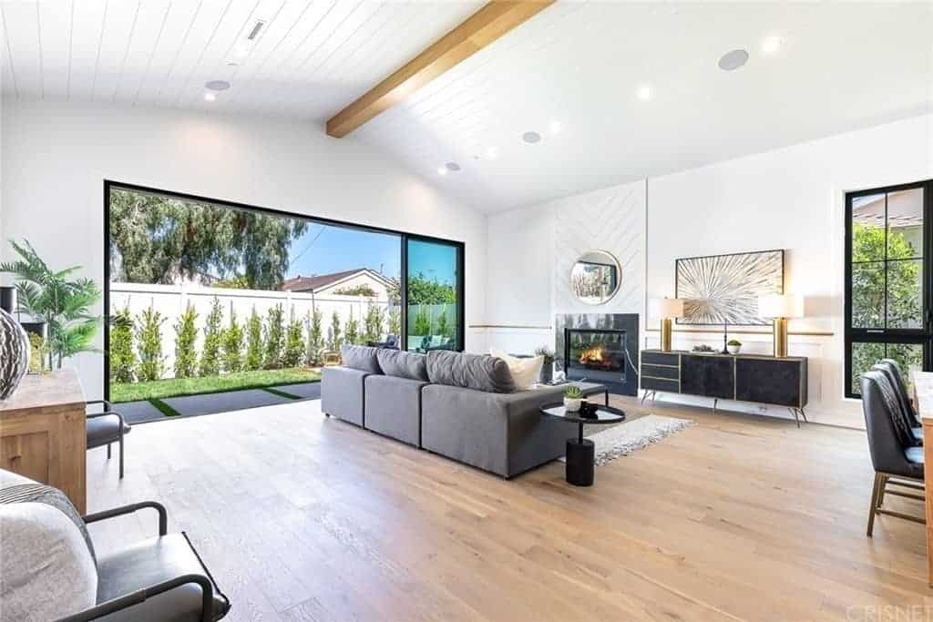 The wide cathedral ceiling with a shiplap plank finish has a single exposed wooden beam running the middle. This is paired with a wide hardwood flooring that is complemented by the gray sectional sofa and the modern fireplace with a dark frame that stands out against the white wall.