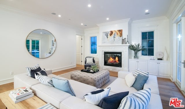 The bright white walls matches with the bright white ceiling that is augmented by recessed lights that shine down on the white mantle of the fireplace that is topped with a colorful painting across from the white L-shaped sectional sofa and its light gray tufted cushioned coffee table.