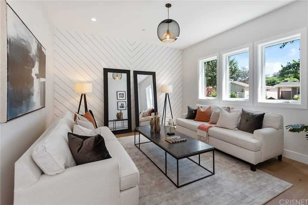 The white wall on the far side has a patterned plank finish and adorned with a couple of tall mirrors flanked by standing lamps. This sets a nice background for the couple of cushioned sofas and the narrow dark coffee table in the middle.