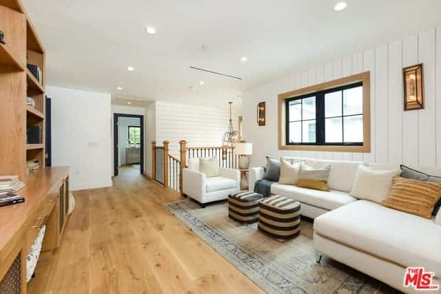 This is a second floor living room right beside the staircase railings. It is against a white wall with a plank finish adorned with a couple of wall lamps flanking the window above the L-shaped sectional sofa facing two striped ottomans.