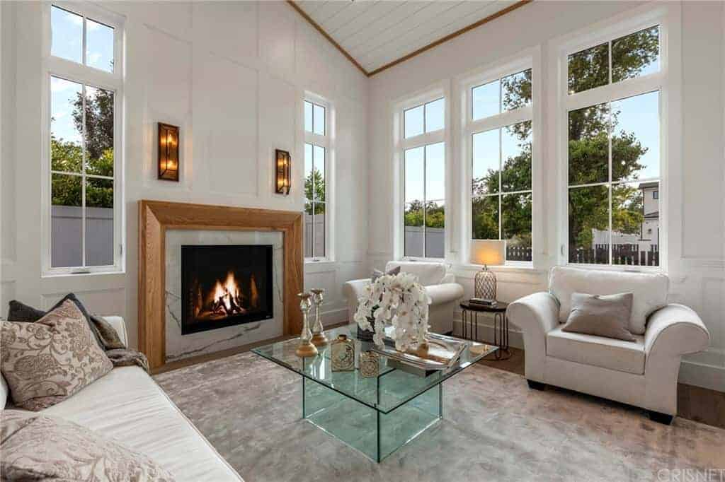 The glass coffee table stands in the middle of the gray area rug flanked by the light gray comfortable sofa and cushioned armchairs brightened by the surrounding tall windows and warmed by the fireplace built into the wall with a wooden mantle.