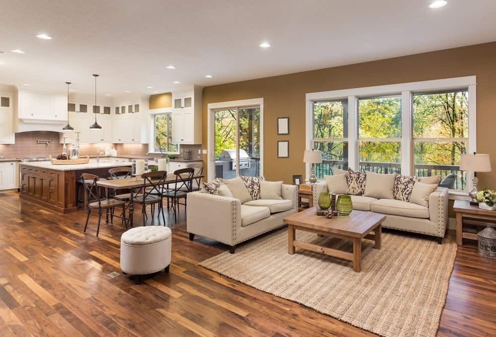 This Farmhouse-style living room has brown walls that match the hardwood flooring and the woven area rug underneath the wooden coffee table. This is paired with a couple of two-seat couches with a light brown hue that complements their wooden end tables.