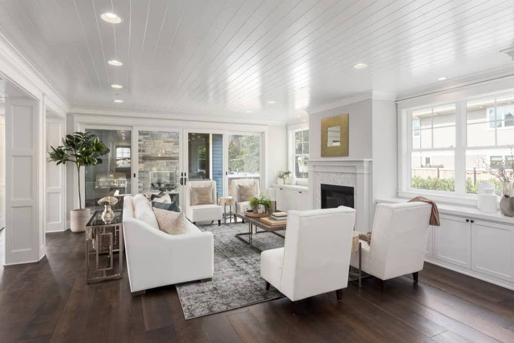 This brilliant living room has a white shiplap ceiling with recessed lights that brighten up the dark hardwood flooring that contrasts the white walls and white sofa set facing a fireplace embedded into the white wall adorned with a golden mirror above.