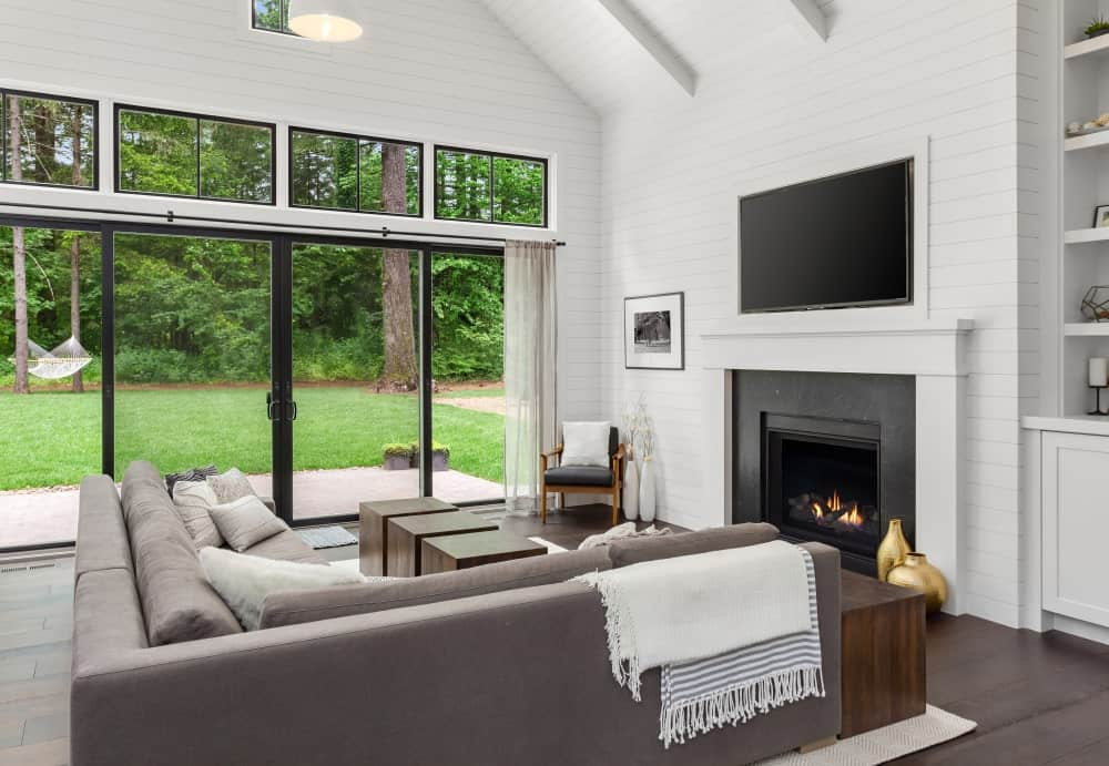 The white cathedral ceiling has a shiplap finish that extends to the white walls that are contrasted by the dark hardwood flooring. This is complemented by the gray L-shaped sectional sofa facing a black fireplace that stands out against the white wall.