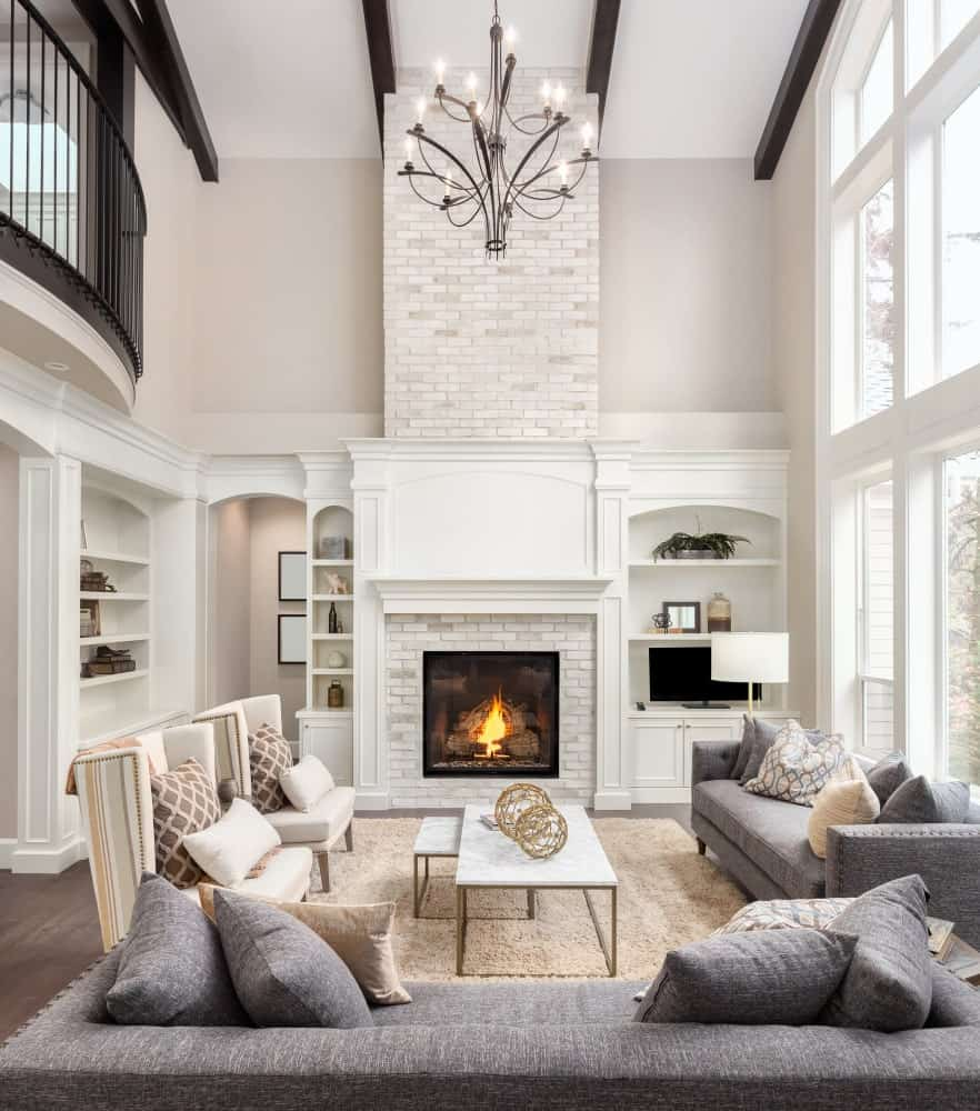 The two gray cushioned couches are facing a nesting coffee table with a white marble top that stands out against the beige area rug underneath. This is facing a charming fireplace that is inlaid with bricks and has a white mantle blending with the wooden structures flanking it that has shelves and cabinets.