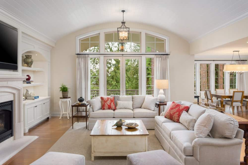 The white cove ceiling is complemented by the beige walls that are dominated by the white framed windows and glass doors. These bring in an abundance of natural lighting that brightens up the beige couches and white shelves and cabinets beside the fireplace.