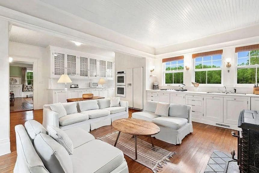 This is a cozy living room that is apparently inside the kitchen. It sits in the middle of the hardwood flooring that is surrounded by kitchen peninsulas with white shaker cabinets and drawers. This matches with the light gray cushioned sofa set surrounding a small elliptical wooden coffee table.