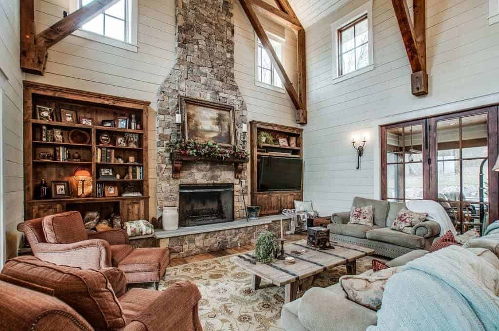 The brown, gray and light gray cushioned sofas and armchairs are all facing a rustic wooden coffee table across from a large wall that is dominated by the large stone column housing the fireplace that is flanked on both side by wooden shelves.
