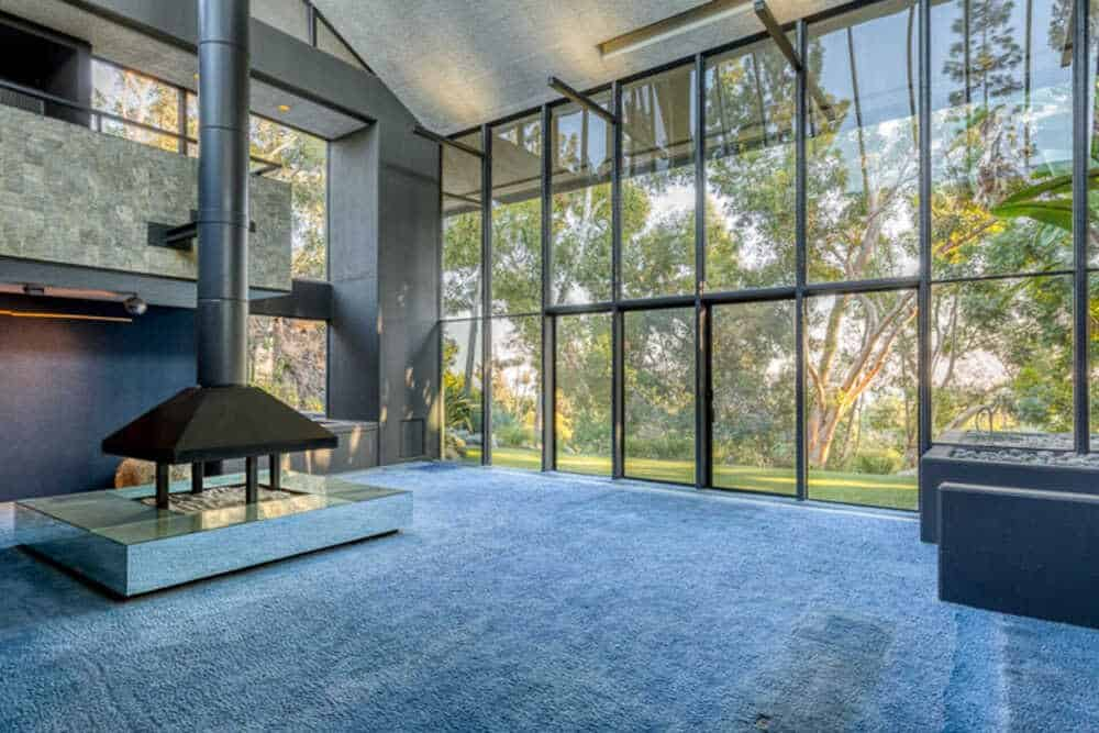 This is a spacious and bright living room with a large glass wall on one side and a freestanding fireplace topped with a tall cathedral ceiling.