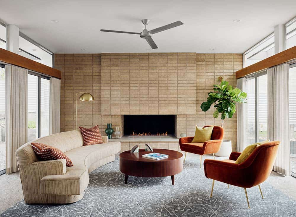 This is the living room with a large curved beige sofa and a couple of orange arm chairs surrounding the round wooden coffee table across from the fireplace that is housed by a large brick wall adorned with a potted plant.