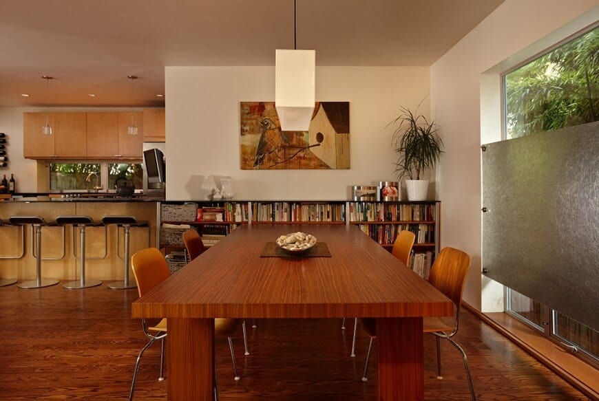 A close up look at this dining table set lighted by a charming pendant lighting. The room also offers a large bookshelf with hundreds of books.