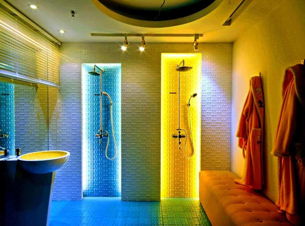 This immensely cool bathroom looks like it came from a science fiction movie with its pair of shower areas that have different-colored lighting. One is blue and one is yellow paired with an orange cushioned bench on the side across from the modern sink.