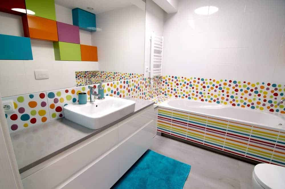 The simple white minimal and modern elements of this simple bathroom such as the white vanity, white sink, toilet and bathtub as well as the white walls and ceiling are all given a whimsical face lift with the addition of rainbow-colored accents.