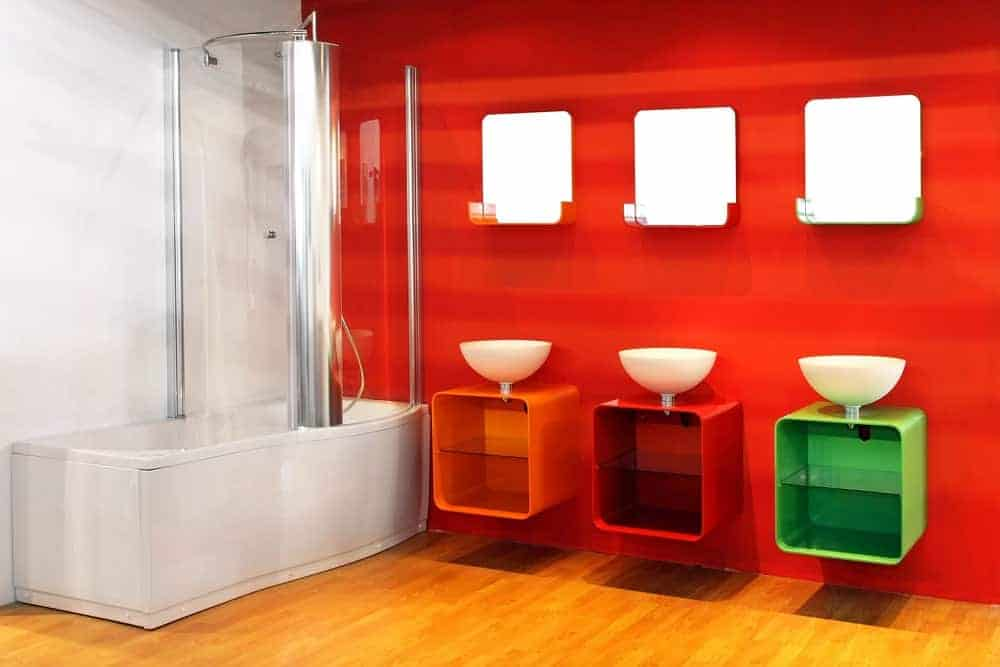 This is a delightful candy-like bathroom that has three modern floating vanities of different colors supporting its own white bowl-shaped sink paired with a simple mirror. This is against a red wall that makes the light gray bathtub and shower area stand out.