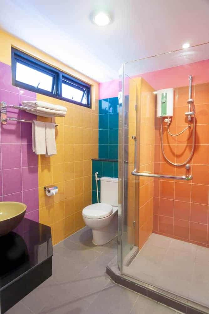 The gray flooring of this simple bathroom provides a median color for the rainbow hues on the wall tiles that together provide a cheerful and whimsical aesthetic to the otherwise simple bathroom.