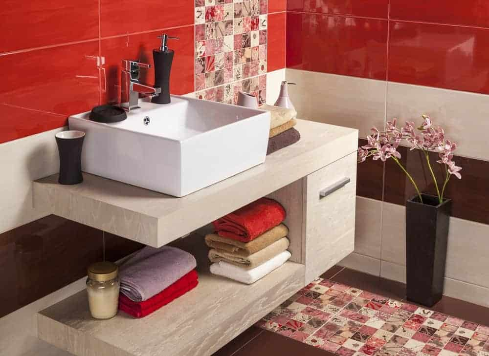 This bathroom has a chic quality to its striped walls of red, white and brown that is traversed with a delightful pink row of patterned tiles that adds a whole new dimension to the beauty of the modern vanity and its modern sink.