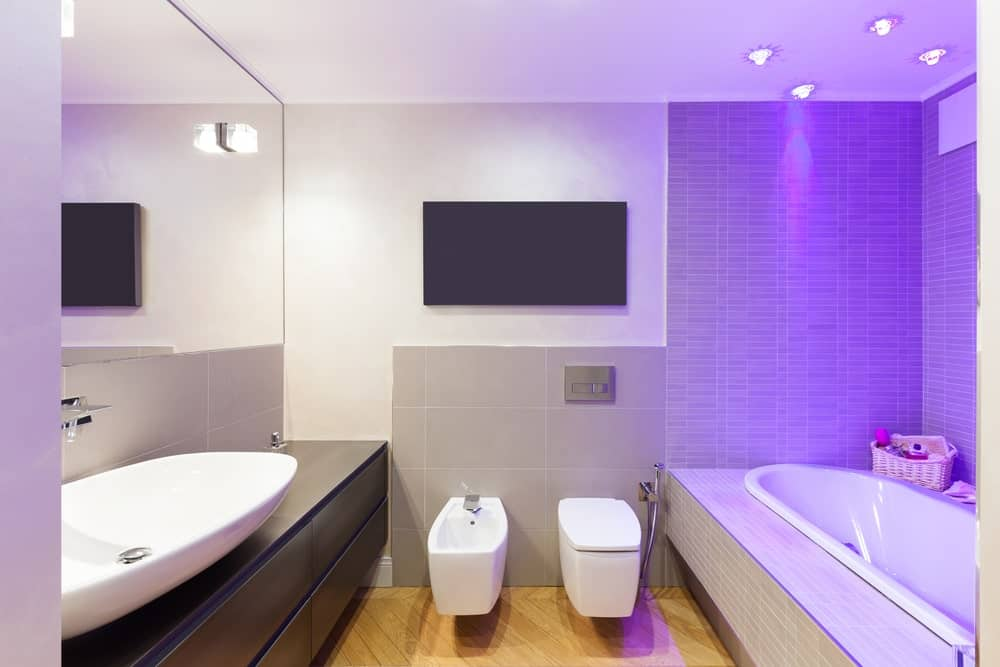 This simple bathroom has a hardwood flooring, white walls accented with gray tiles and a white bowl sink that matches the white bathtub. This aesthetic is elevated with the addition of blue-purple lights shining down on the bathtub.