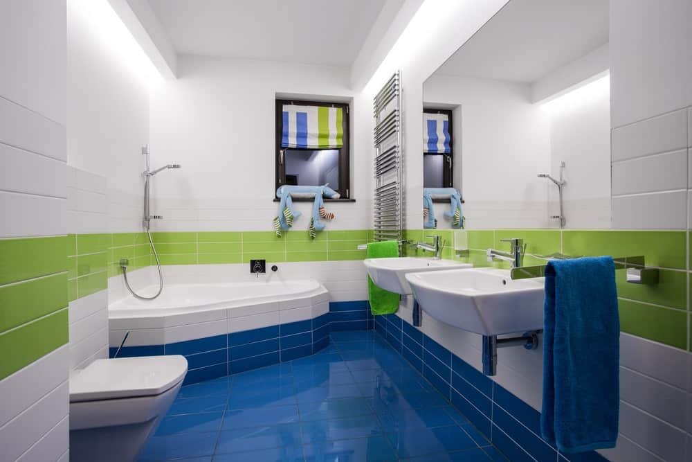 This is a fun and cheery bathroom with its blue floor tiles reaching to the lower part of the walls. This is then followed with a strip of white tiles and then green tiles right in the middle. This elevates the simple design of a corner bathtub and two white floating sinks.