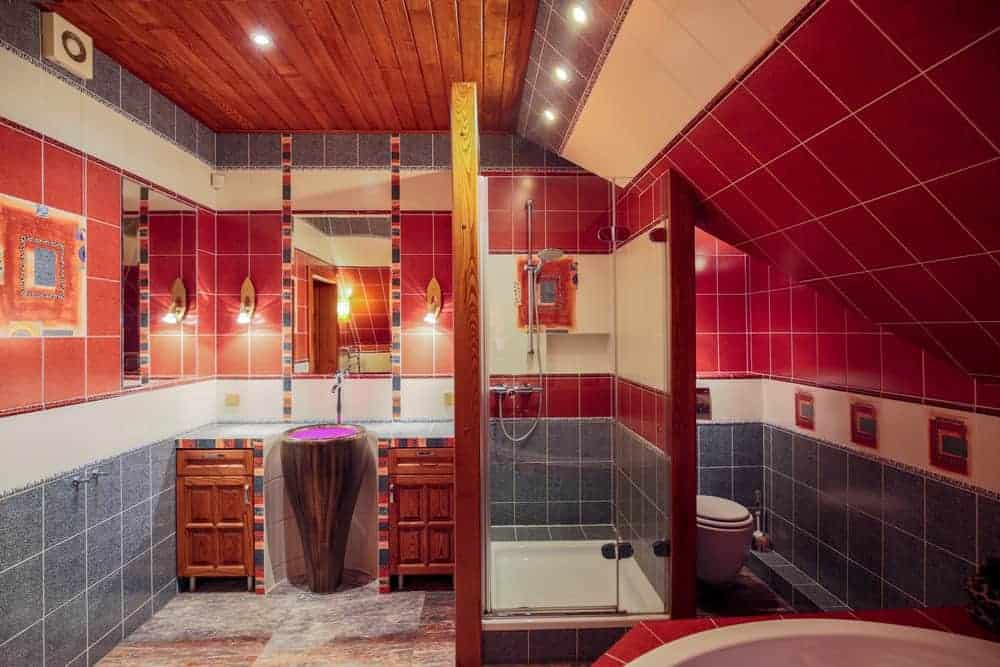 The red upper walls of this bathroom goes well with the wooden ceiling and the wooden vanity cabinets flanking the pedestal of the sink. The lower part of the walls have gray hue to it that complements the marble flooring.