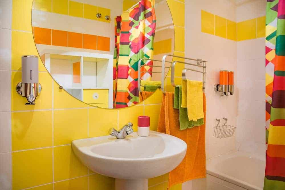 The white pedestal sink is a nice complement to the yellow tiles of the walls adorned with a round vanity mirror and modern bathroom fixtures. This colorful demeanor is further augmented by the colorful shower curtain of the white shower area.