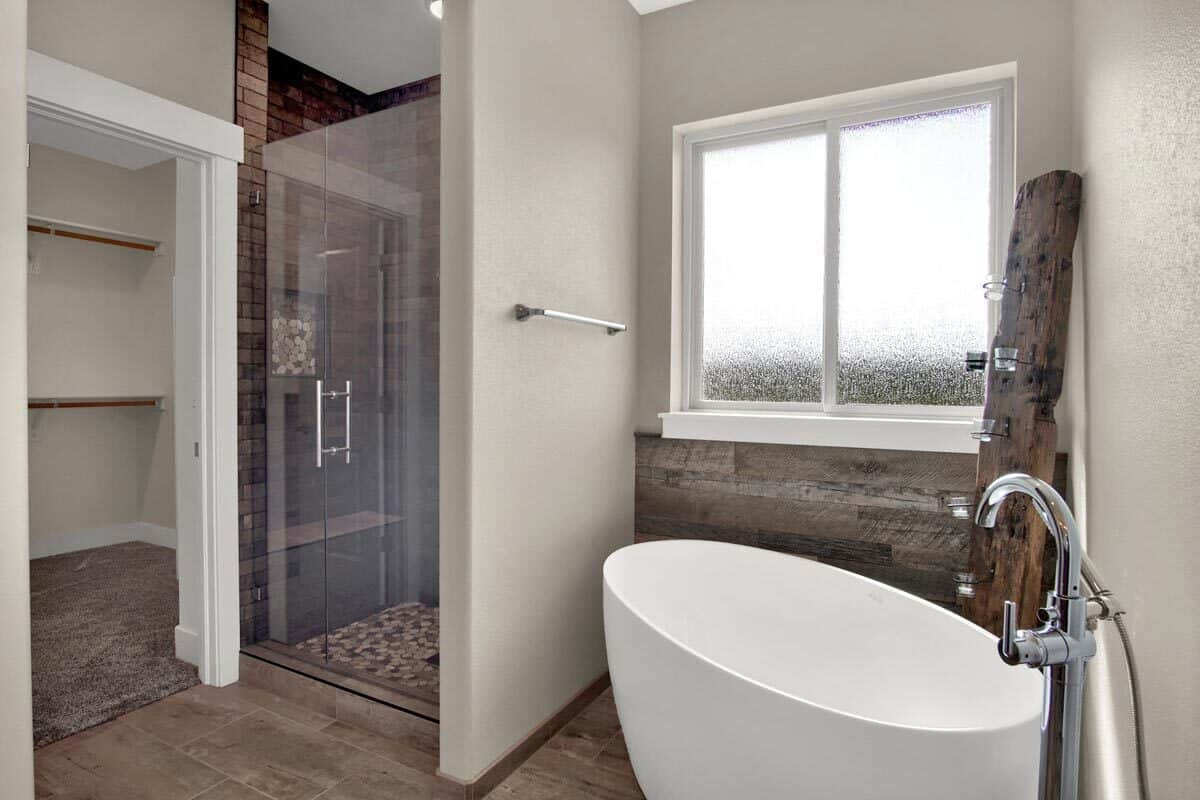 This primary bathroom is equipped with a walk-in closet, a shower area, and a freestanding tub complemented with rustic timber that serves as a candle holder.