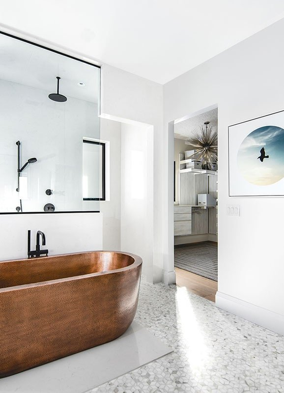 The freestanding tub with a copper finish stands out against the pristine white walls and patterned tile flooring of this primary bathroom.