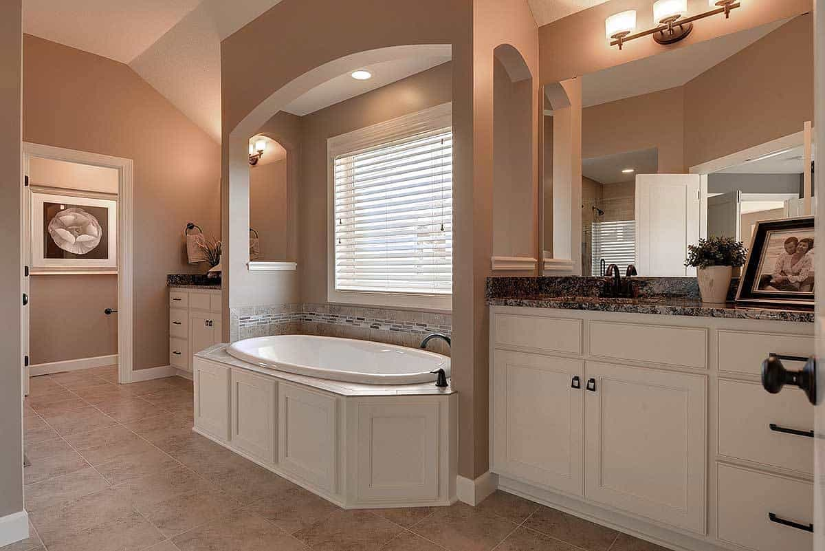 This homey and luxurious bathroom has earthy beige tones to its flooring and walls that complements the white cabinets that match the housing of the bathtub under the window.