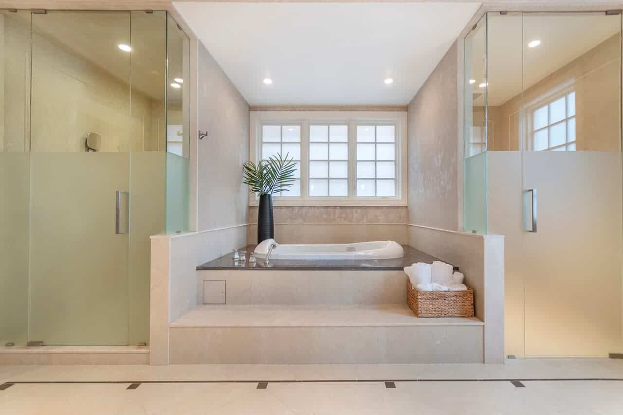 This charming primary bathroom has a bathtub inlaid in a lovely alcove in between two frosted glass encased walk-in showers. The bathtub has a gray countertop that complements the beige walls and flooring.