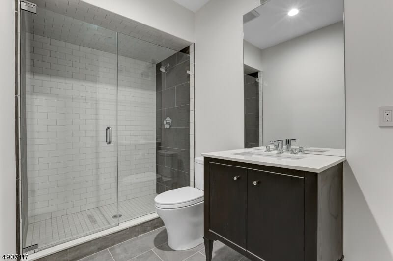 The black vanity with built-in cabinets stands out against the white walls, white toilet as well as the white countertop that is paired with a borderless mirror that matches with the glass door of the shower area.
