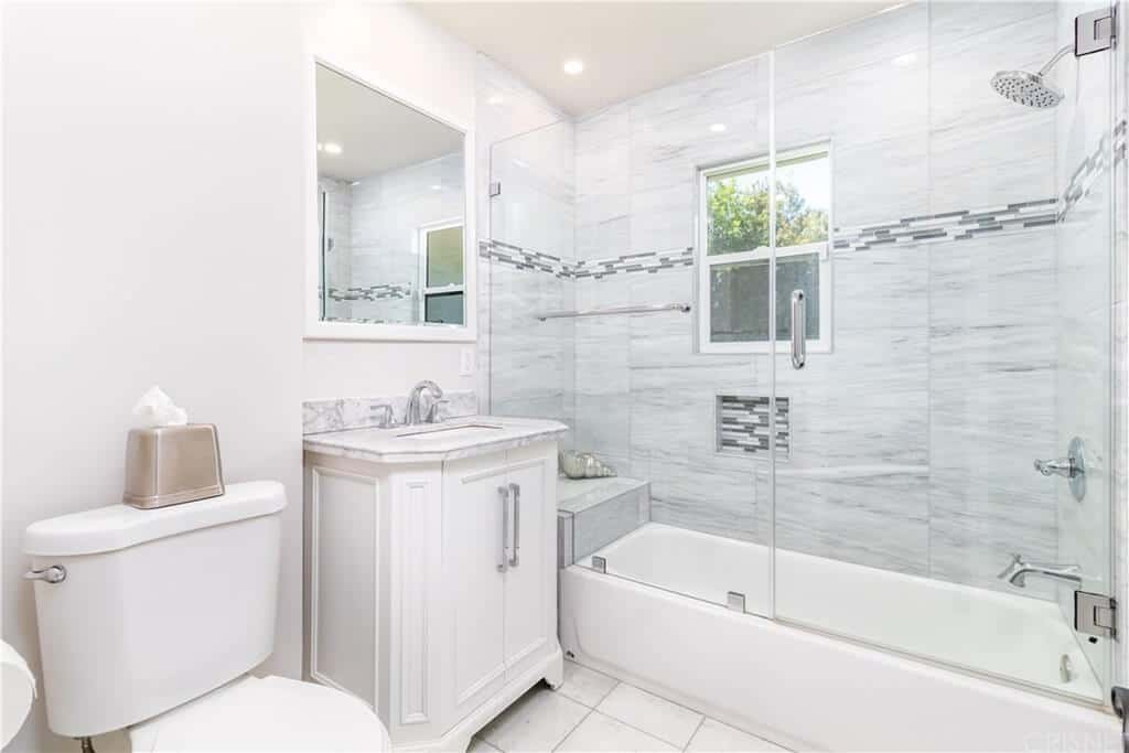 The white toilet, vanity and bathtub blend in with the white tiles of the flooring complemented by the white marble countertop of the vanity that matches with the marble tiled walls of the glass-enclosed shower area.