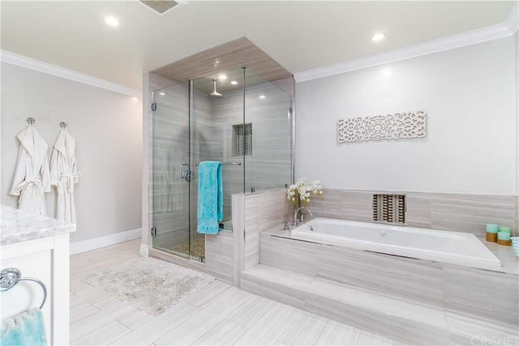 The glass enclosed shower area of this primary bathroom is placed in a corner beside the bathtub that is inlaid with gray tiles that extend to the floors and the walls of the shower area that has an overhead shower.