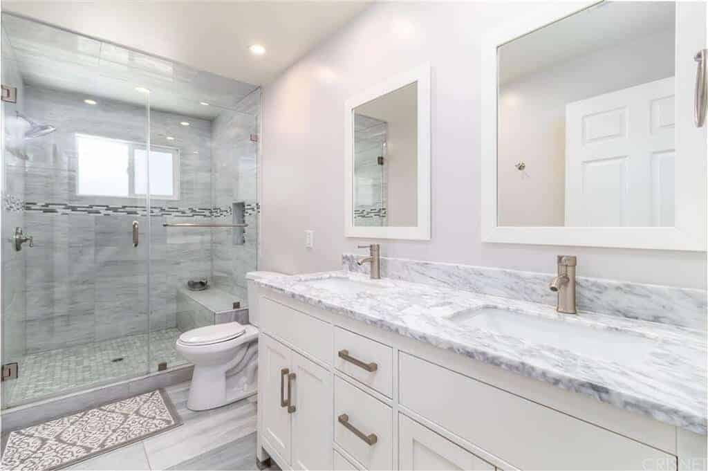 The white cabinets and drawers of the vanity has brass handles that pair well with the faucets of the two sinks inlaid with white marble countertop complemented by the two white framed vanity mirrors above.