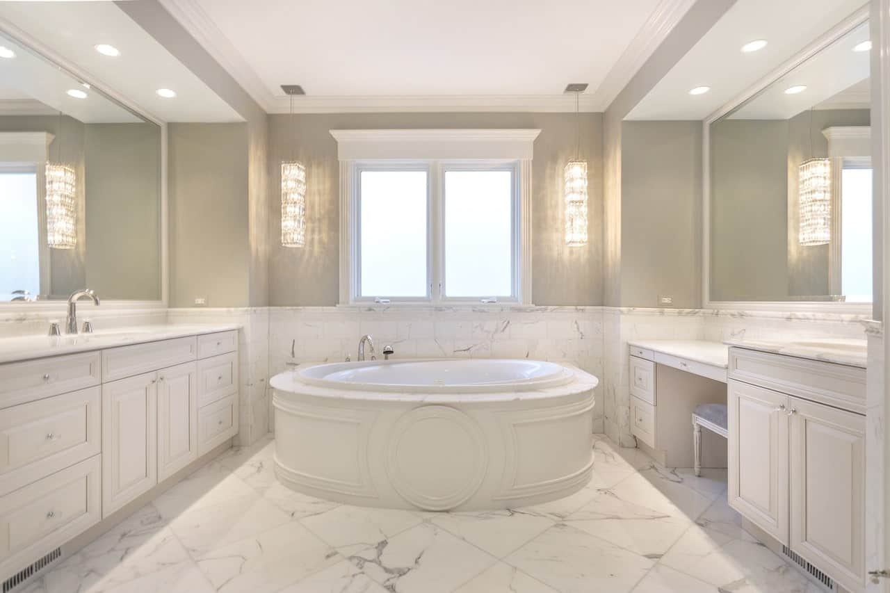 This lovely Transitional-Style bathroom has a white ceiling bordered with white molding that contrasts the gray walls lit with a pair of elongated pendant lights flanking the window above the round bathtub with a nice white finish.