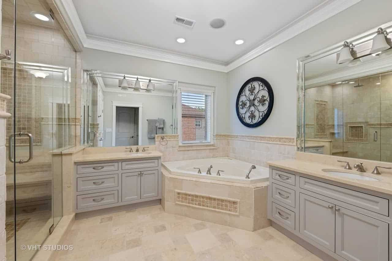 This charming primary bathroom has two vanity areas flanking a corner bathtub inlaid with the same beige tiles as the flooring and adorned with an intricate circular artwork mounted on the wall above.