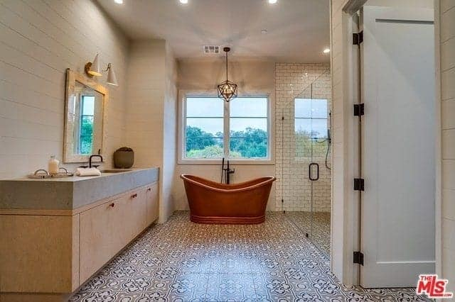 The complex patterns of the floor tiles are complemented by the brass freestanding bathtub placed at the far wall with a window and geometric pendant light above it with a glass-enclosed shower area beside it.