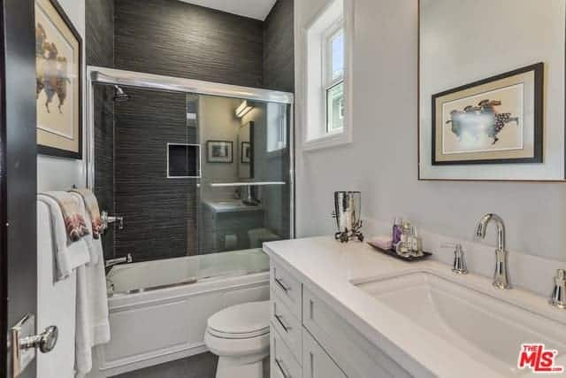 The walls of the shower area has black tiles that match the flooring tiles contrasting the white toilet and countertop of the sink area topped with a vanity mirror that reflects the artwork on the wall across.