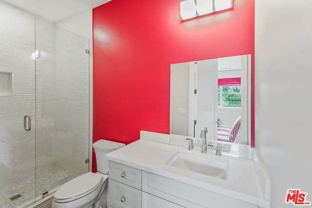 The bright pink wall behind the white toilet provides a nice colorful contrast to the white vanity and shower area that has a glass door matching the borderless vanity mirror over the white countertop.