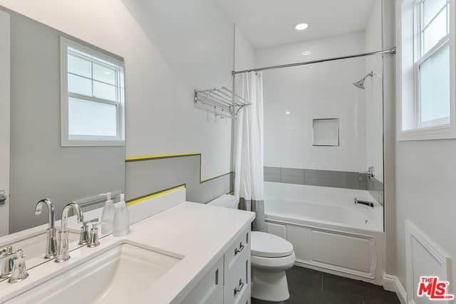 The white walls of this simple bathroom has gray tiles lining the middle part extending to the bathtub that also funsctions as the shower area that has a white and gray shower curtain over a black-tiled flooring.