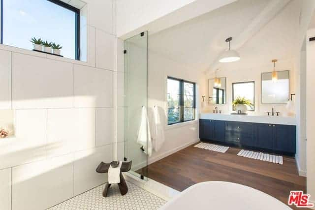The white irregular arched ceiling is contrasted by the hardwood flooring of this primary bathroom that has a navy vanity that stands out against the white walls along with its white countertop illuminated by hanging pendant lights.