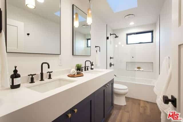 The blue vanity has a thick white countertop that is contrasted by the black farmhouse-style faucets that matches the fixtures of the shower area that has a glass wall beside the white toilet contrasting the hardwood flooring.