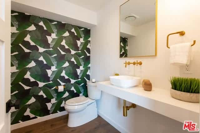 The wall beside the white toilet that stands out against the dark hardwood flooring is dominated by green leafy patterns that complement the white wall of the white hanging vanity with gold accents.