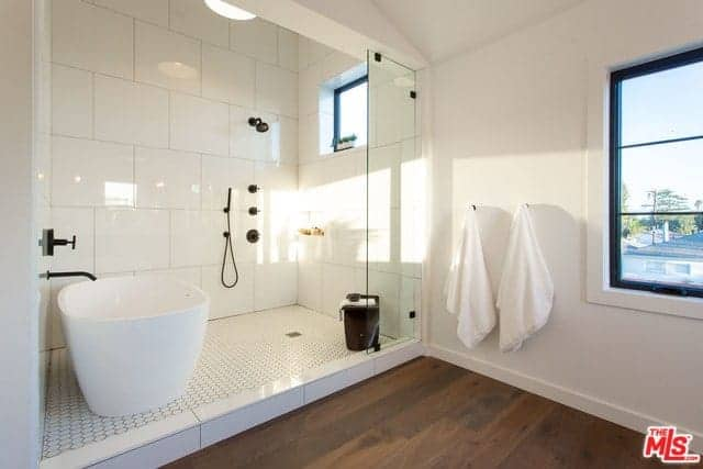 The dark hardwood flooring is contrasted by the large shower area that has white tiles on its floors and walls. This area is also where the freestanding bathtub is placed paired with a black faucet matching the shower fixtures.