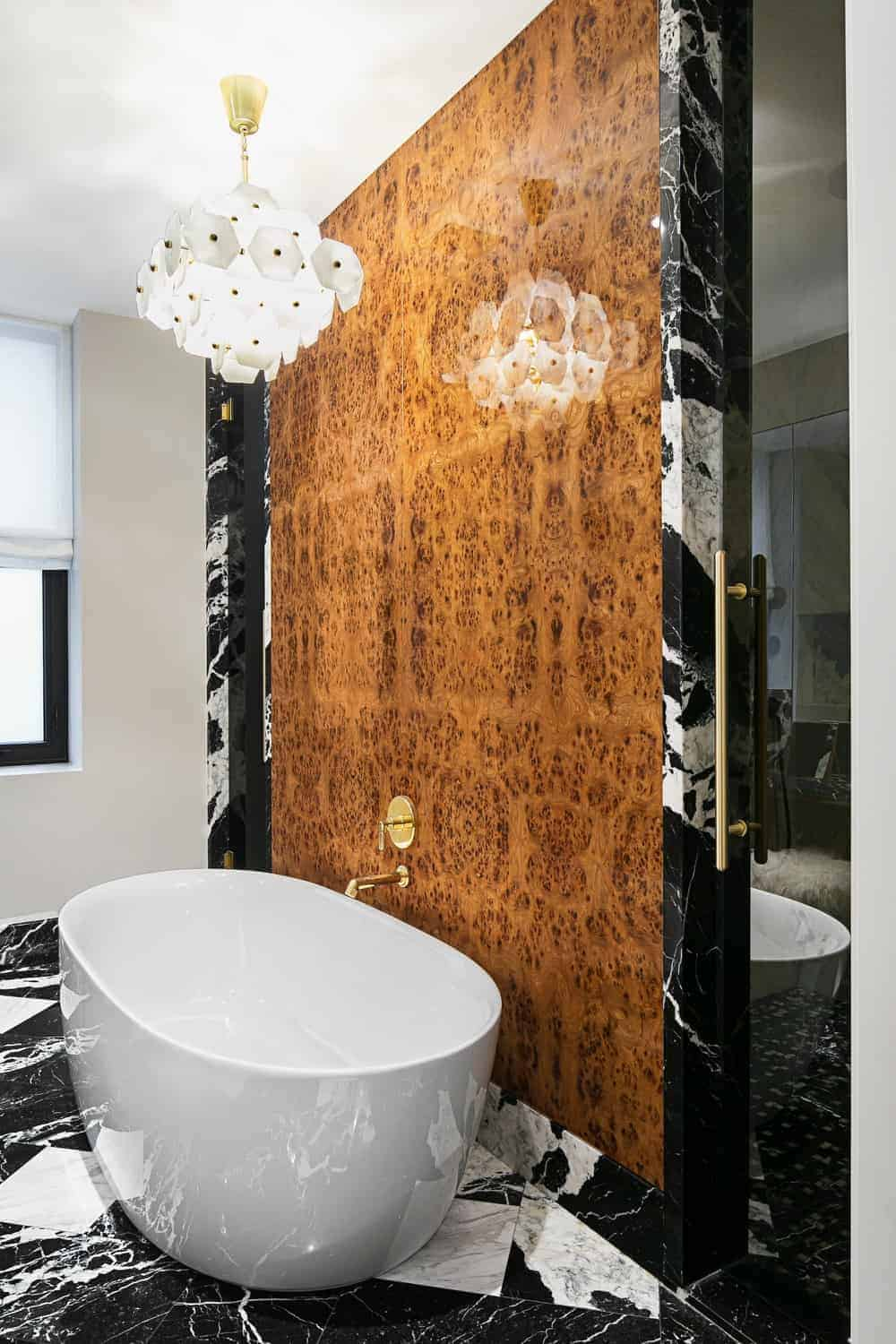This charming bathroom oozes with elegance in its elliptical freestanding bathtub that stands out against the black and white marble tiles of the flooring extending to the frame of the brown wall that houses the golden faucet.